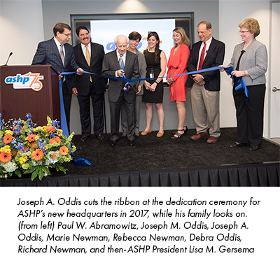 Joseph A. Oddis cuts the ribbon at the dedication ceremony for ASHP's new headquarters in 2017, while his family looks on. (from left) Paul W. Abramowitz, Joseph M. Oddis, Joseph A. Oddis, Marie Newman, Rebecca Newman, Debra Oddis, Richard Newman, and then-ASHP President Lisa M. Gersema
