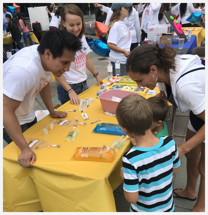 Pharmacy Students from  Massachusetts College of Pharmacy and Health Sciences answer questions from children at pharmacy carnival.